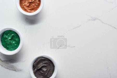 Photo pour Vue du haut des tasses avec divers produits naturels de beauté sur la surface de marbre - image libre de droit