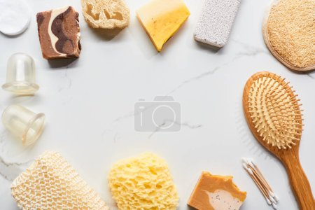 Photo for Top view of massage jars, hair brush, bath sponge, loofah and pumice stone on marble surface - Royalty Free Image