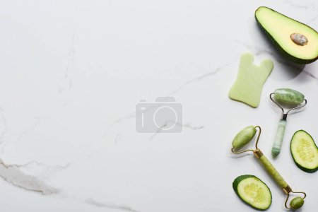 Photo for Top view of massage rollers and pieces of cucumber and avocado on marble surface - Royalty Free Image