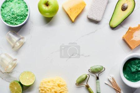 Photo pour Vue du haut des pots de massage, des rouleaux faciaux, de l'éponge de bain, de la pierre ponce et des fruits et légumes frais sur la surface de marbre - image libre de droit