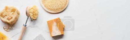 Photo pour Coup panoramique de l'éponge de visage, du loofah, du pinceau de corps et du savon sur la surface de marbre - image libre de droit