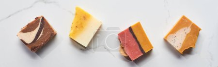 Photo pour Coup panoramique de morceaux de savon naturels faits maison sur la surface de marbre - image libre de droit