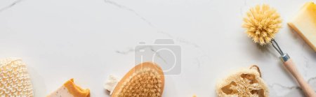 Photo pour Coup panoramique de loofah, brosses de corps, savon et éponge de bain sur la surface de marbre - image libre de droit