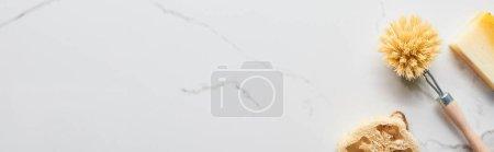Photo pour Coup panoramique de loofah, brosse de corps et morceau de savon sur la surface de marbre - image libre de droit
