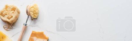 Photo pour Coup panoramique de brosse de corps, savon naturel et loofah sur la surface de marbre - image libre de droit