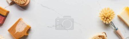 Photo pour Coup panoramique de brosses de corps et de morceaux de savon naturels sur la surface de marbre - image libre de droit