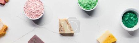 Photo pour Coup panoramique de tasses avec des produits de beauté naturels et du savon sur la surface de marbre - image libre de droit