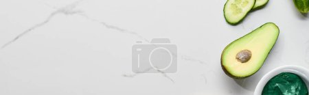 Photo for Panoramic shot of green beauty product, avocado and cucumber on marble surface - Royalty Free Image