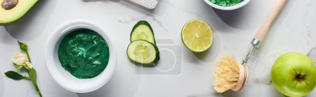 panoramic shot of natural beauty product and body brush near cucumber slices, lime, avocado and green apple on marble surface