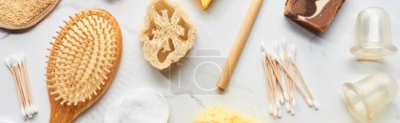 Photo pour Coup panoramique d'écouvillons de coton, brosse à cheveux, pots à vide de massage et loofah sur la surface de marbre - image libre de droit