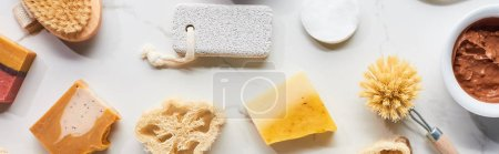 Photo pour Coup panoramique de loofah, pierre ponce, brosses pour le corps, tampons de coton et savon fait maison sur la surface de marbre - image libre de droit