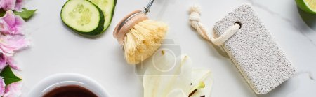 Photo for Panoramic shot of pumice stone, body brush near fresh flowers and cucumber slices on marble surface - Royalty Free Image