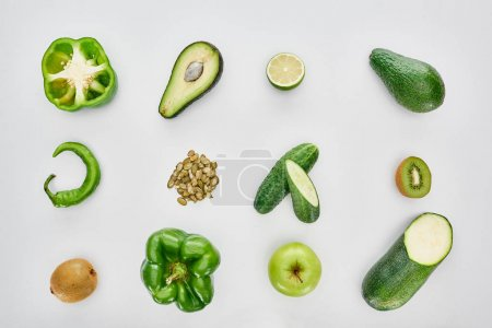 Photo for Top view of apple, avocados, cucumbers, lime, peppers, pumpkin seeds and zucchini - Royalty Free Image