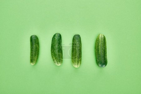 Photo for Top view of fresh and whole cucumbers on green background - Royalty Free Image
