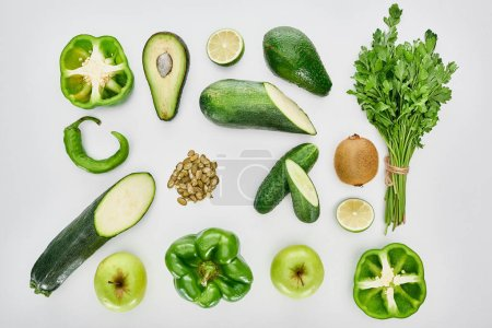 Photo for Top view of apples, avocados, cucumbers, limes, peppers, kiwi, pumpkin seeds, greenery and zucchini - Royalty Free Image