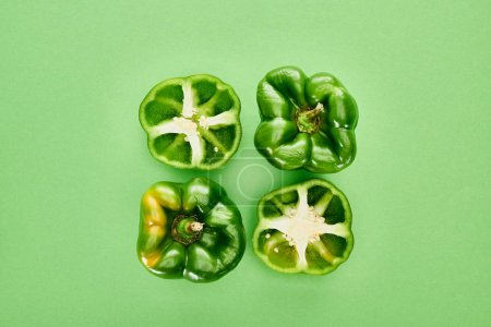 Photo for Top view of fresh and organic peppers on green background - Royalty Free Image