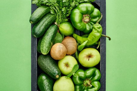 Photo for Top view of apples, avocados, cucumbers, peppers, kiwi, greenery and zucchini in wooden box - Royalty Free Image