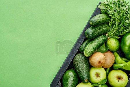 Photo for Top view of apples, avocados, cucumbers, peppers, kiwi, greenery in wooden box - Royalty Free Image