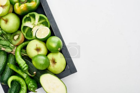 Photo for Top view of apples, limes, peppers, kiwi, cucumbers and zucchini in wooden box - Royalty Free Image