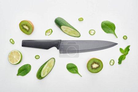 Foto de Vista superior de pepinos, kiwi, limas, pimientos, vegetación y cuchillo - Imagen libre de derechos