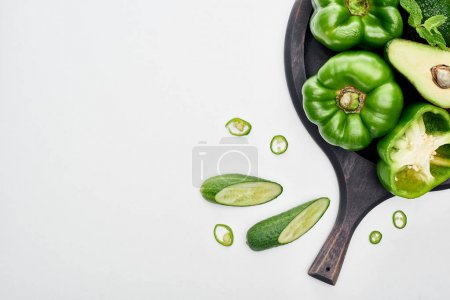 Photo for Top view of avocado, peppers, cucumbers and greenery on pizza skillet - Royalty Free Image