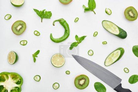 Foto de Vista superior del cuchillo, pepinos frescos, kiwi, limas, pimientos y vegetación - Imagen libre de derechos