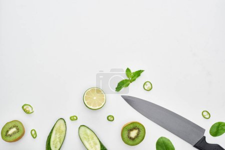 Photo for Top view of knife, fresh cucumbers, kiwi, lime, peppers and greenery - Royalty Free Image