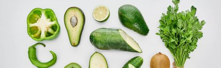 Photo for Panoramic shot of peppers, cucumber, zucchini, kiwi, lime, greenery and avocados - Royalty Free Image