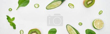 Foto de Foto panorámica de pepinos frescos, kiwi, lima, pimientos y vegetación - Imagen libre de derechos
