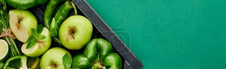 Photo for Panoramic shot of fresh and green peppers, apples and greenery in wooden box - Royalty Free Image