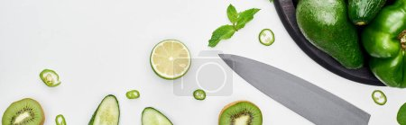 Photo for Panoramic shot of knife, fresh cucumbers, kiwi, lime, peppers and greenery on pizza skillet - Royalty Free Image