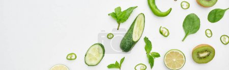 Photo for Panoramic shot of fresh cucumbers, kiwi, limes, peppers and greenery - Royalty Free Image