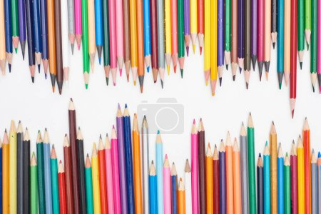 Photo for Two lines of different sizes color pencils isolated on white - Royalty Free Image