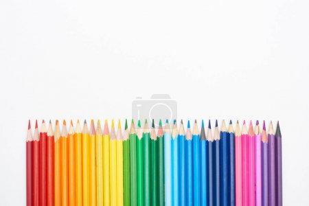 Photo pour Spectre arc-en-ciel composé d'une rangée droite de crayons de couleur isolés sur du blanc - image libre de droit