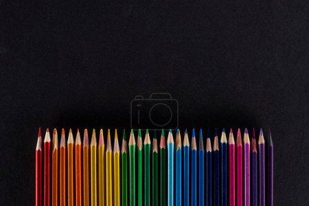 Photo pour Spectre arc-en-ciel composé d'une rangée droite de crayons de couleur isolés sur du noir - image libre de droit