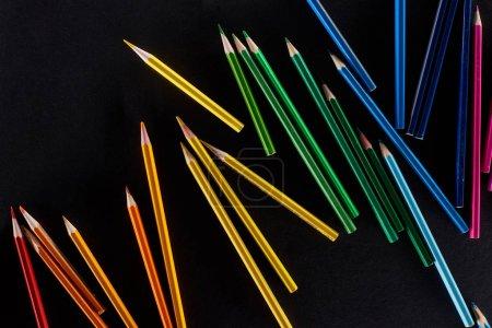 Photo pour Crayons de couleur aiguisés dispersés d'isolement sur le noir - image libre de droit