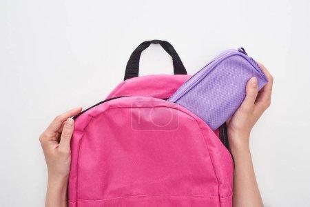 Photo pour Vue partielle de l'écolière prenant le cas crayon violet de cartable rose isolé sur blanc - image libre de droit