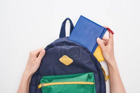Photo pour Vue cultivée d'écolière prenant le bloc-notes du sac d'école bleu d'isolement sur le blanc - image libre de droit