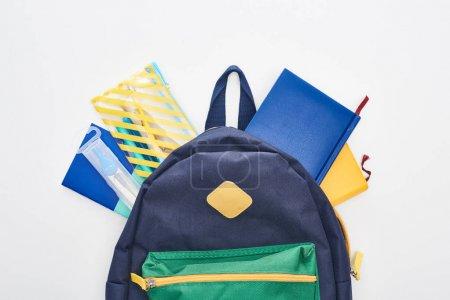 Photo pour Sac d'école bleu avec différents approvisionnements d'école d'isolement sur le blanc - image libre de droit