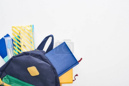 Photo for Blue schoolbag with notepads, pencil case and school supplies isolated on white - Royalty Free Image