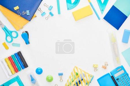 Photo pour Vue supérieure des fournitures scolaires dispersées bleues et jaunes d'isolement sur le blanc - image libre de droit
