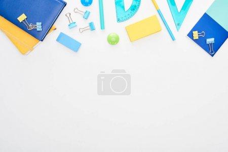 Photo pour Vue supérieure des fournitures scolaires dispersées bleues et jaunes avec des bloc-notes d'isolement sur le blanc - image libre de droit