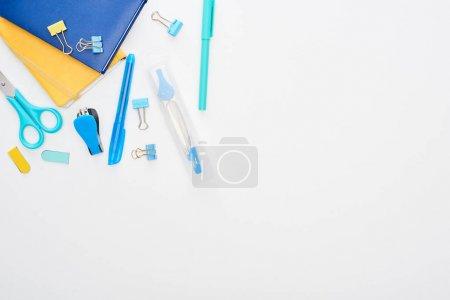 Photo pour Vue supérieure des fournitures scolaires dispersées bleues près des bloc-notes d'isolement sur le blanc - image libre de droit