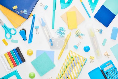 Photo for Top view of blue and yellow scattered school supplies with notepads, pencil case and calculator isolated on white - Royalty Free Image