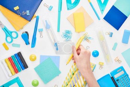 Photo pour Image cultivée d'écolière retenant le stylo jaune près de la papeterie d'isolement sur le blanc - image libre de droit