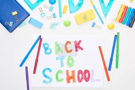 Photo for Top view of paper with back to school lettering near colorful felt-tip pens and stationery isolated on white - Royalty Free Image