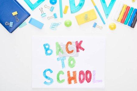 Photo pour Vue supérieure du papier avec le texte de retour à l'école près des fournitures scolaires d'isolement sur le blanc - image libre de droit