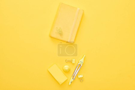 Photo for Top view of yellow notepad and stationery on same background - Royalty Free Image