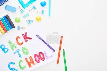 Photo pour Vue supérieure du papier avec le texte de retour à l'école près des stylos colorés de feutre-bout et des fournitures scolaires d'isolement sur le blanc - image libre de droit