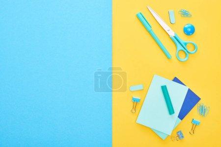 Photo pour Vue supérieure de la papeterie bleue différente avec des feuilles de papier sur le fond bicolor - image libre de droit